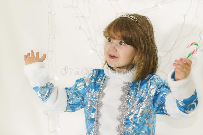 Happy girl in a blue costume of snow maiden with astonishment he waved a candy cane royalty free stock images
