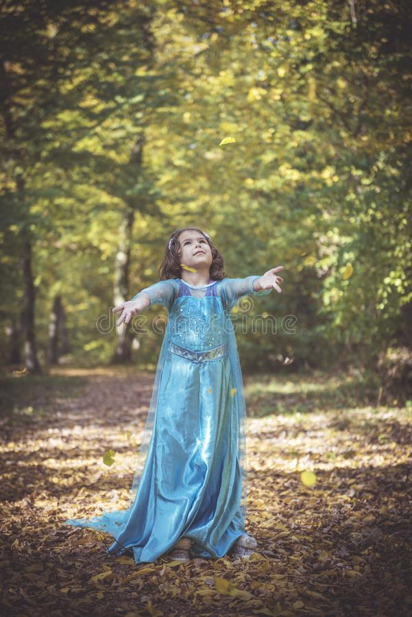 Little fashionable girl. Happy girl in blue dress playing with leaves in the woods,selective focus royalty free stock photography