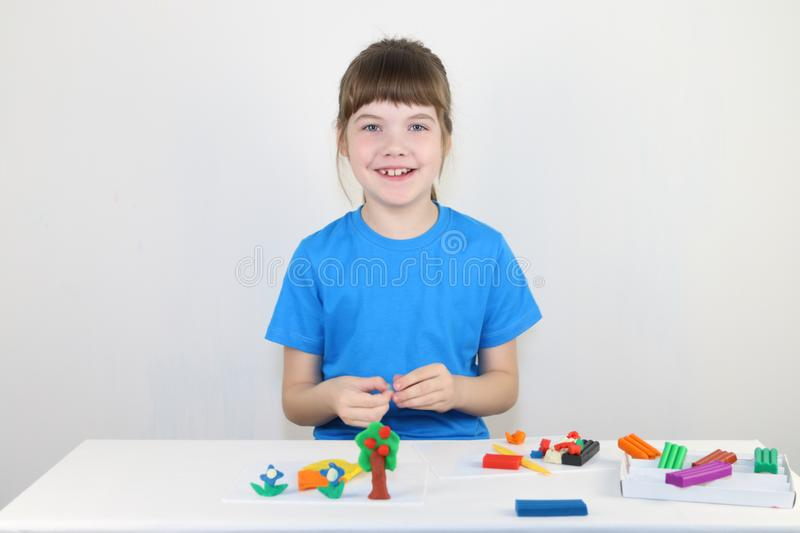 Happy girl in blue molds from plasticine on white table stock image