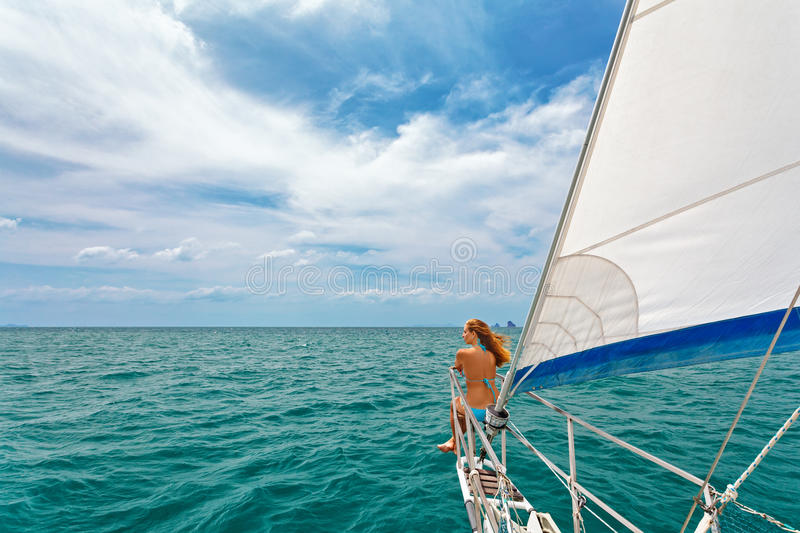 Happy girl on board of sailing yacht have a fun. stock photo