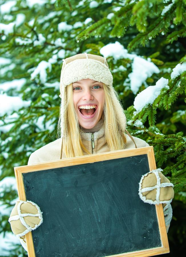 Happy girl with a board for winter advertising. Announcement. Discounts for winter. Seasonal sale. Warm clothes. Shop stock image