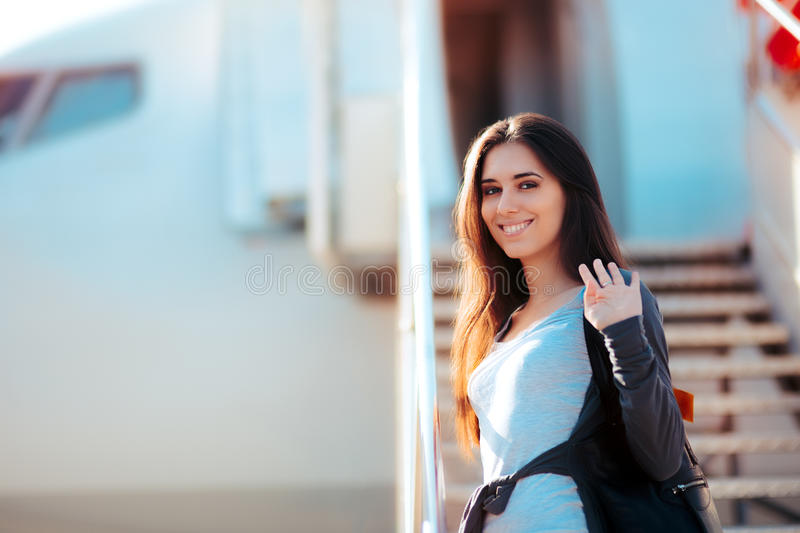 Happy Girl Boarding Airplane and Waving Goodbye. Woman standing on the boarding stairs of a plane stock photo