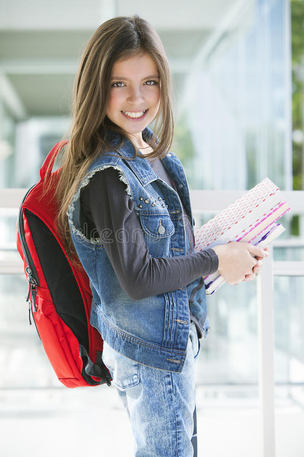 Happy girl with books and backpack. Happy girl smiling with books and backpack, back to shcool royalty free stock image