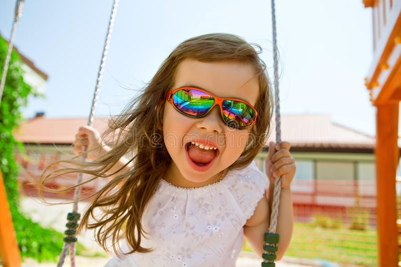 Happy girl in bright rainbow glasses swinging on a swing. Happy child in glasses swinging on a swing on a Sunny summer day royalty free stock photo