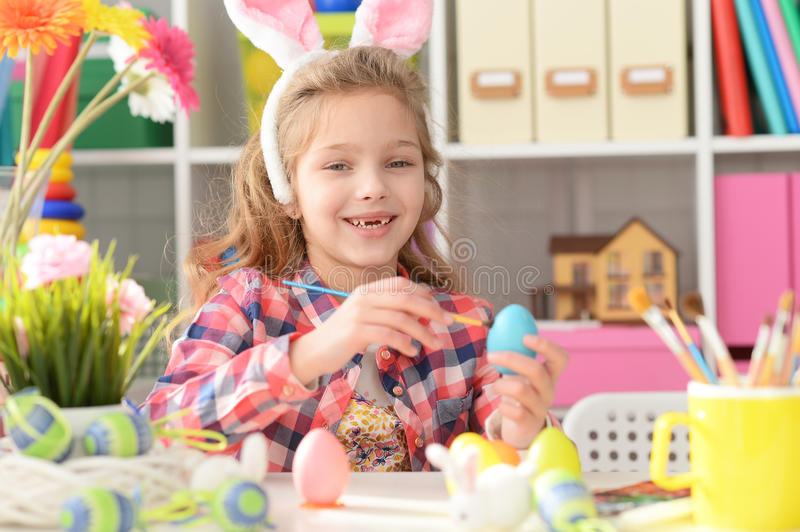 Happy girl with bunny ears getting ready for Easter. And color eggs royalty free stock photography