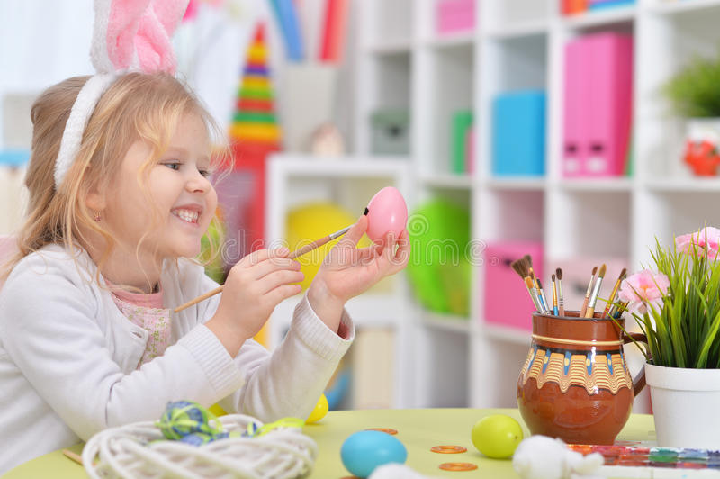 Happy girl with bunny ears getting ready for Easter. And color eggs royalty free stock photos