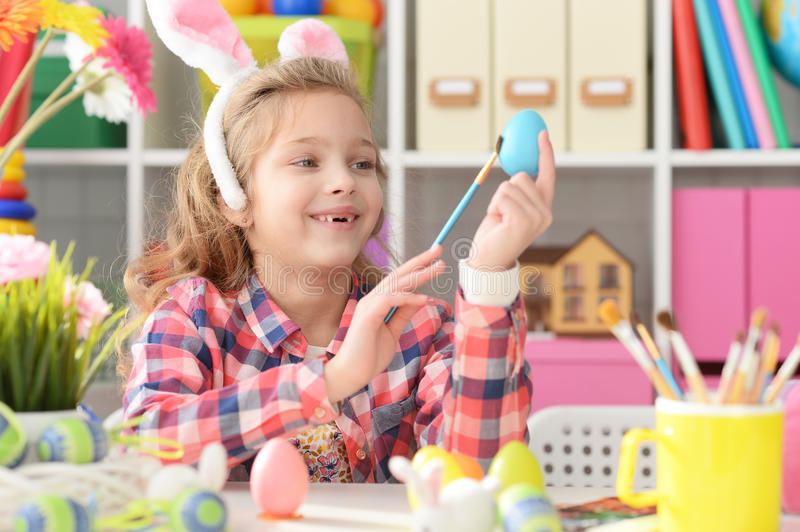 Happy girl with bunny ears getting ready for Easter. And color eggs royalty free stock images