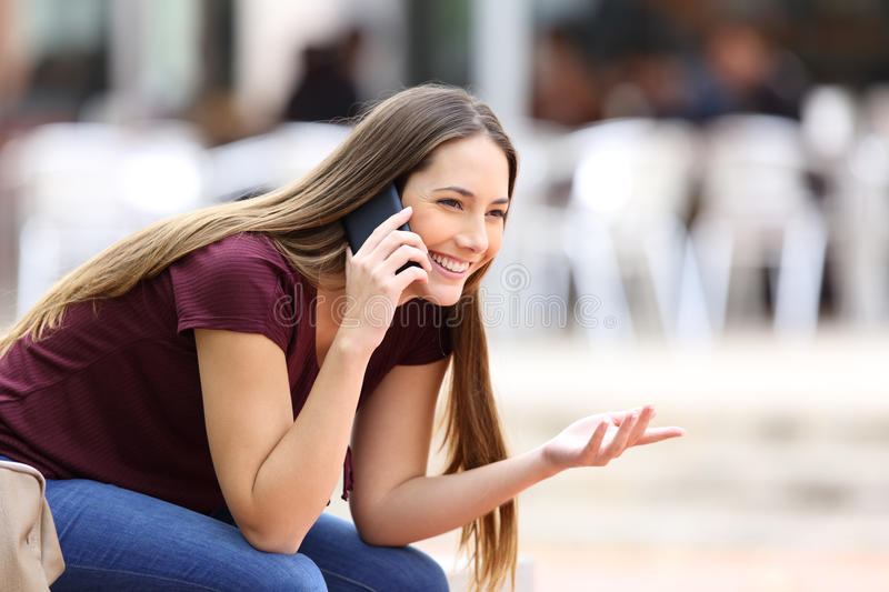 Happy girl calling on mobile phone. Looking away sitting on a bench in the street royalty free stock photos