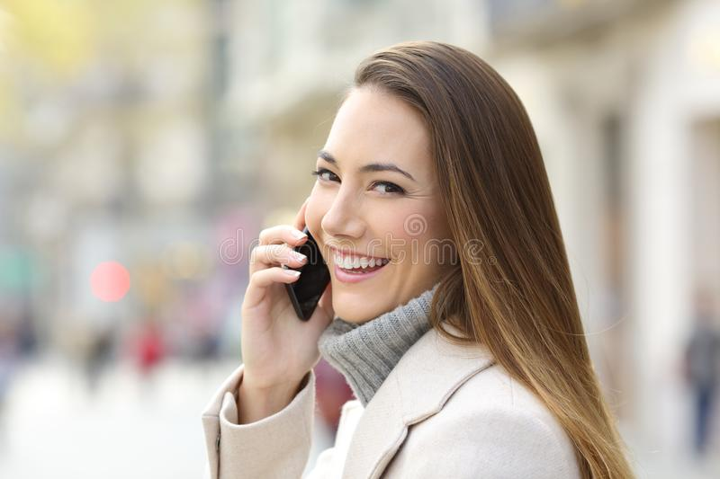 Happy girl calling on phone in winter and looking you. Portrait of a happy girl calling on phone in winter and looking you on the street royalty free stock image