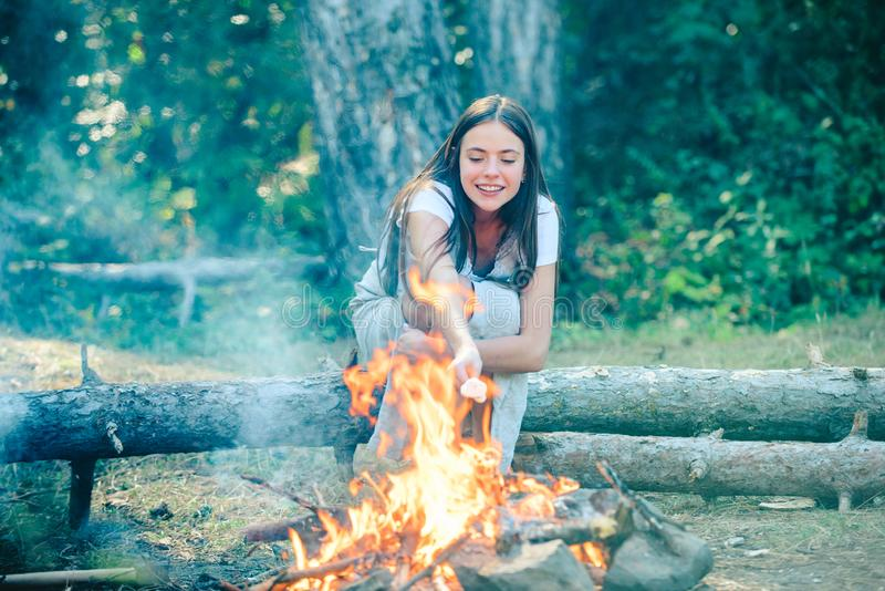 Happy girl on a camping trip relaxing by campfire. Girl backpackers relaxing near campfire. stock image