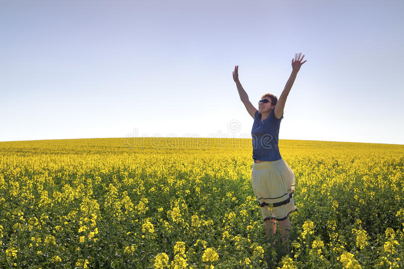 Download Happy Girl Among Canola Plants Under Blue Sky Stock Photo - Image: 24823906