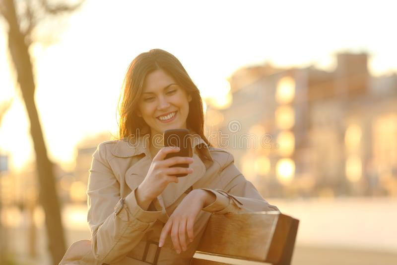 Happy girl checking smart phone at sunset on a bench stock images