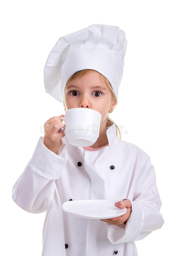 Happy girl chef white uniform isolated on white background. Drinking from the white cup holding a saucer. Portrait image royalty free stock photo