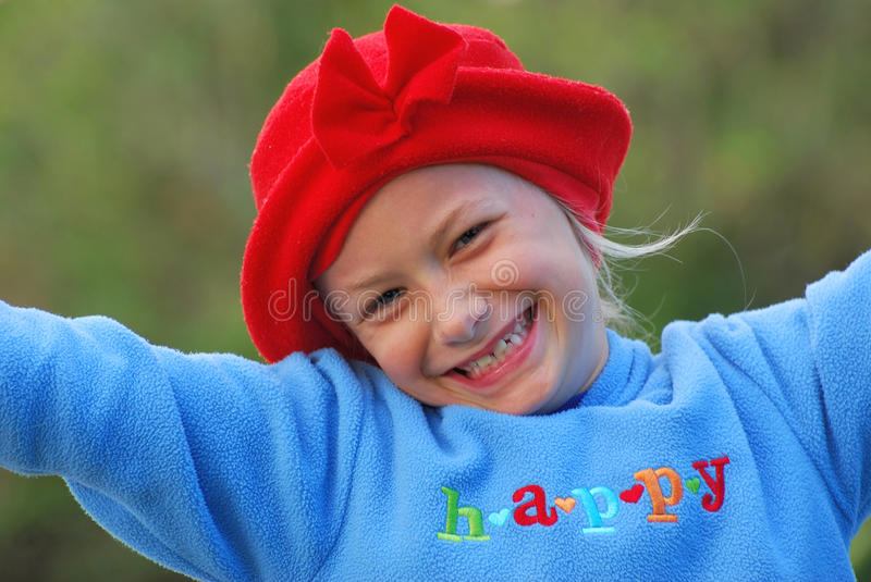 Happy girl child. Outdoor head portrait of a cute little Caucasian girl child with happy smiling facial expression wearing a red hat and a blue jersey in fall royalty free stock photo
