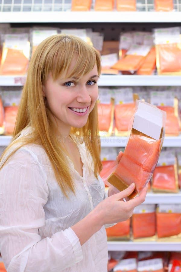 Happy girl chooses salmon in store stock photo