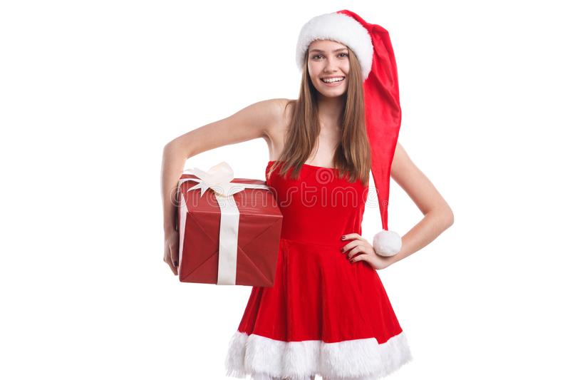 A happy girl in a Christmas dress and hat, holding a gift box and smiling sweetly. Isolated. stock image