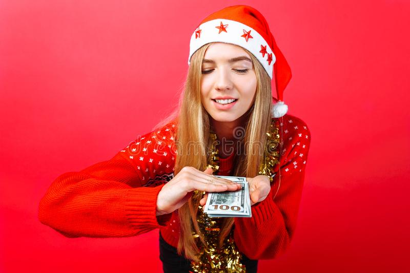 A happy girl in a Christmas hat and with tinsel on her neck, with dollars in her hands, spends money isolated on a red background stock photos