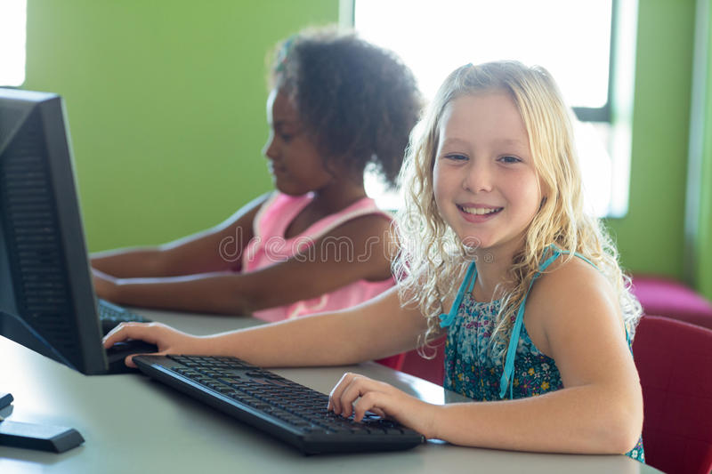 Happy girl with classmate using computers. Portrait of happy girl with classmate using computers in classroom royalty free stock images
