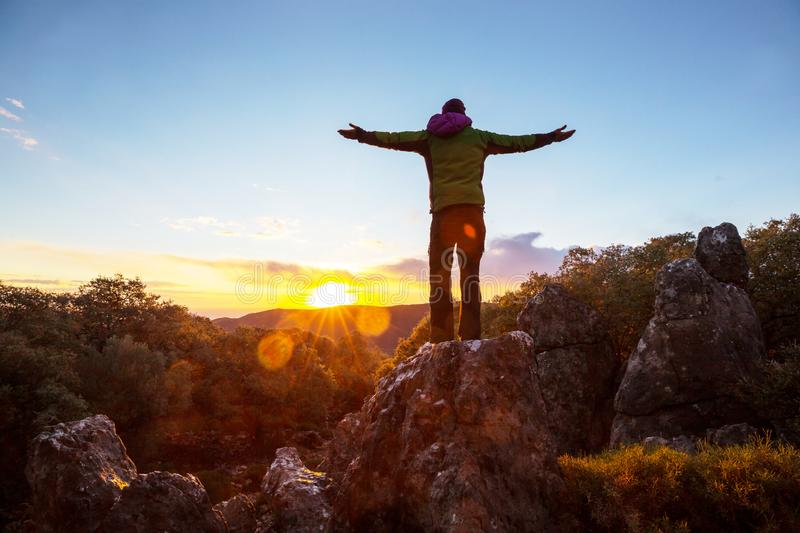 Happy girl. On the cliff at sunrise royalty free stock image