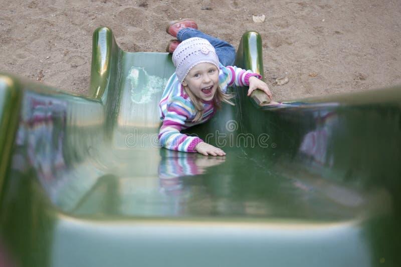 Happy girl climbing on children's slide stock photo