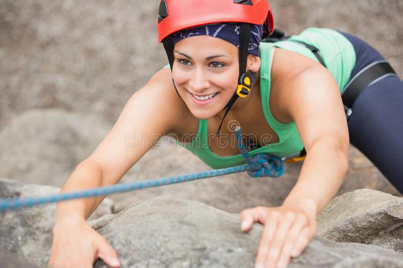 Happy girl climbing rock face. Wearing red helmet stock images