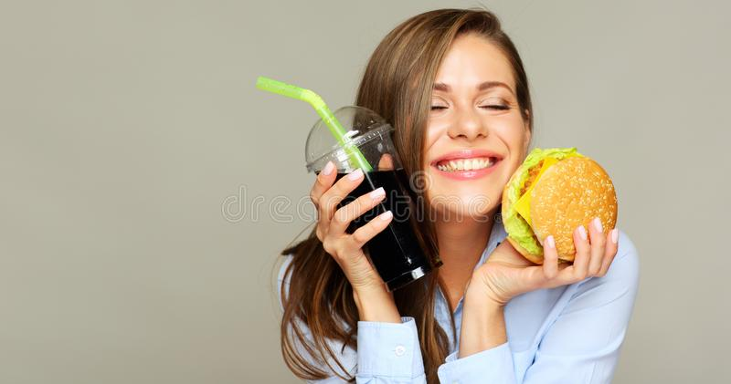 Happy girl closed eyes and smiling with fast food burger and col. A drink. Isolated studio portrait stock photos