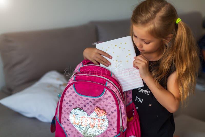 Happy girl collecting school bag. Nice kid prepairing for school her backpack stock images