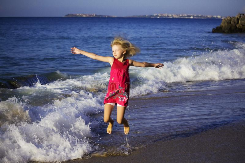 Happy girl in colored dress jumping on the waves on the beach stock photography