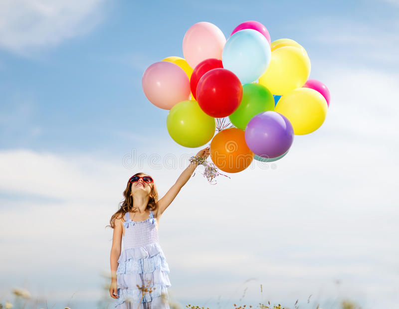 Happy girl with colorful balloons. Summer holidays, celebration, family, children and people concept - happy girl with colorful balloons royalty free stock image