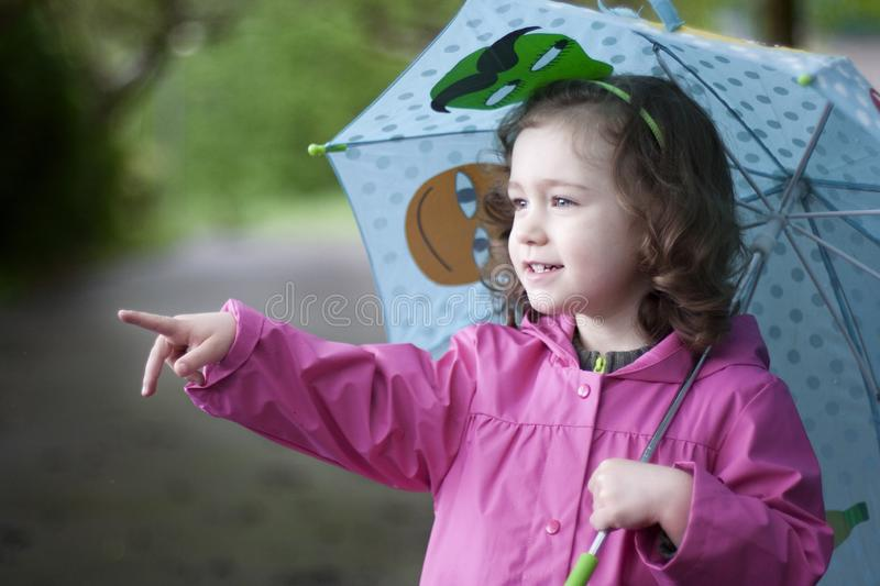 A happy girl with a colorful umbrella. A happy girl, with a colorful umbrella and a pink raincoat, points something out with her finger royalty free stock photo