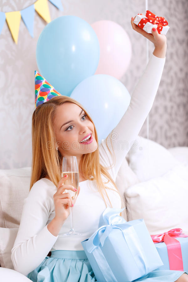 Happy girl on a couch celebrating. Portrait of a young beautiful blond girl sitting on a couch holding a small present above her head surrounded by colorful royalty free stock images