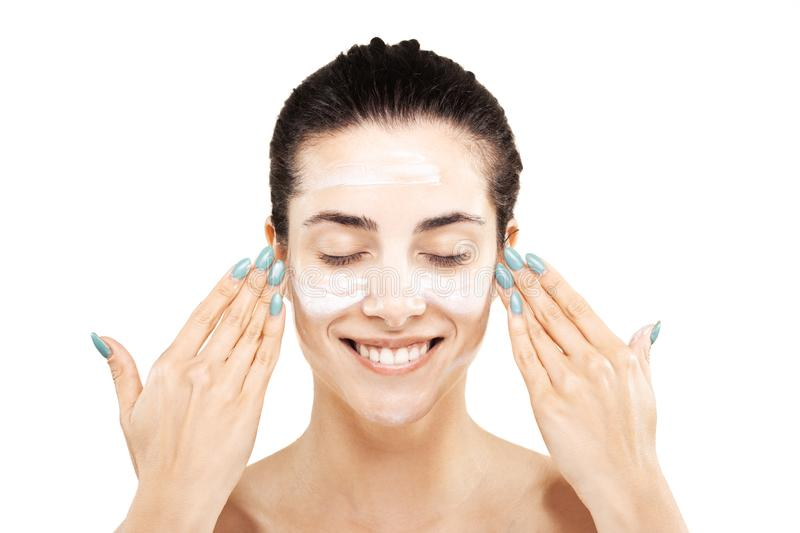 Happy girl with cream on her face stock image