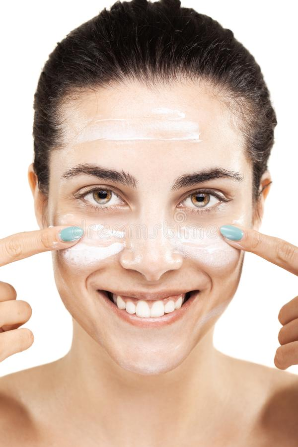 Happy girl with cream on her face stock photo