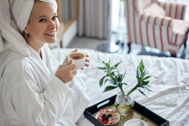 Happy Girl with a Cup of Coffee. Home Style Relaxation Woman Wearing Bathrobe and Towel after Shower. Spa Good Morning royalty free stock photos