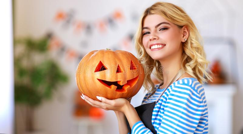 Happy girl is cutting  pumpkin and is preparing for holiday Halloween. Happy girl is cutting a pumpkin and is preparing for the holiday Halloween royalty free stock photography