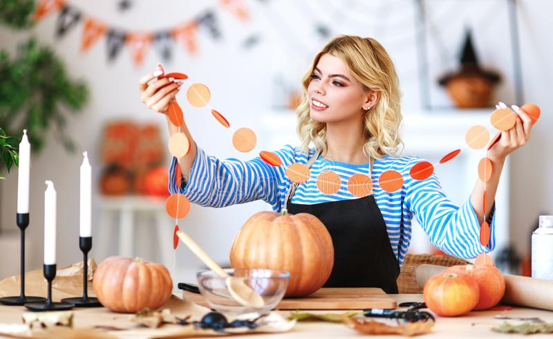 Happy girl is cutting  pumpkin and is preparing for holiday Halloween. Happy girl is cutting a pumpkin and is preparing for the holiday Halloween stock images