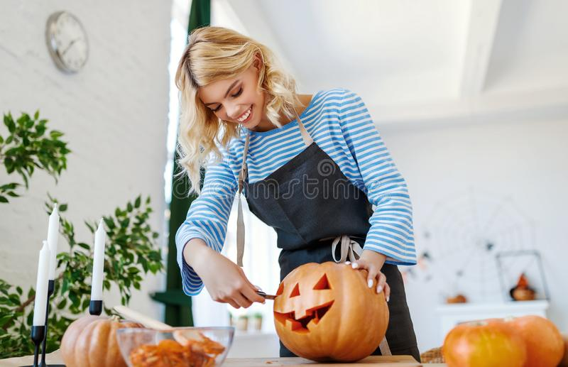 Happy girl is cutting  pumpkin and is preparing for holiday Halloween. Happy girl is cutting a pumpkin and is preparing for the holiday Halloween royalty free stock photos
