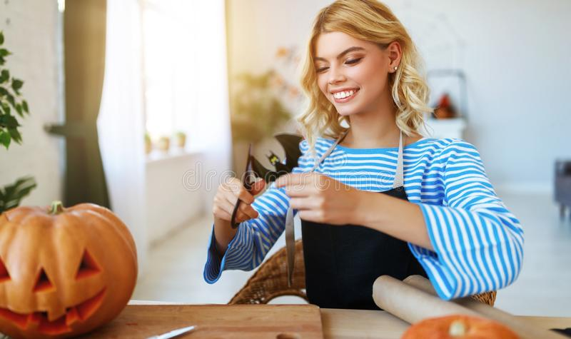 Happy girl is cutting  pumpkin and is preparing for holiday Halloween. Happy girl is cutting a pumpkin and is preparing for the holiday Halloween stock photography
