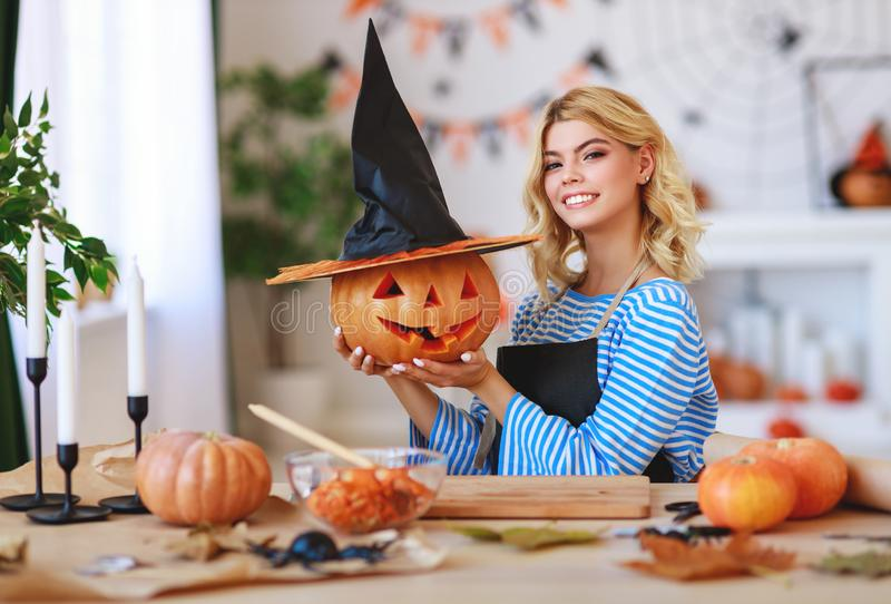 Happy girl is cutting  pumpkin and is preparing for holiday Halloween. Happy girl is cutting a pumpkin and is preparing for the holiday Halloween royalty free stock photo