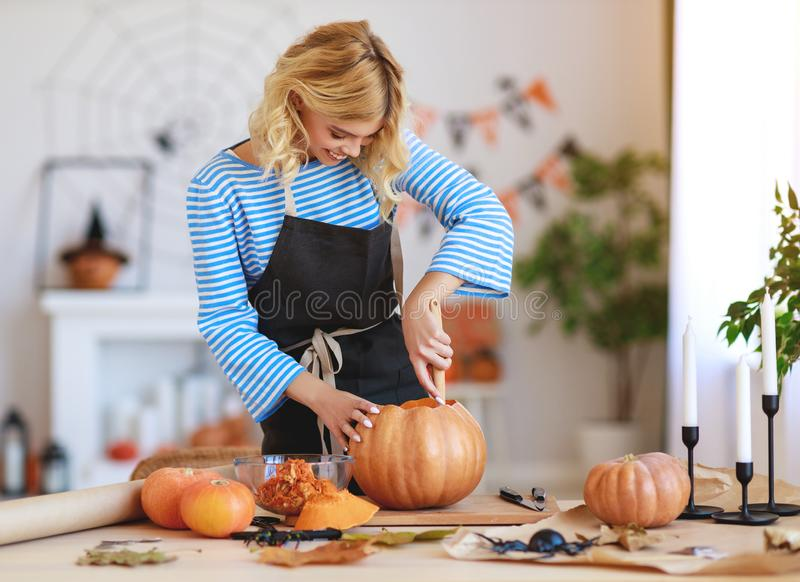Happy girl is cutting  pumpkin and is preparing for holiday Halloween. Happy girl is cutting a pumpkin and is preparing for the holiday Halloween stock image