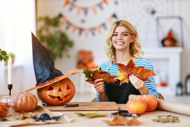 Happy girl is cutting  pumpkin and is preparing for holiday Halloween. Happy girl is cutting a pumpkin and is preparing for the holiday Halloween royalty free stock image