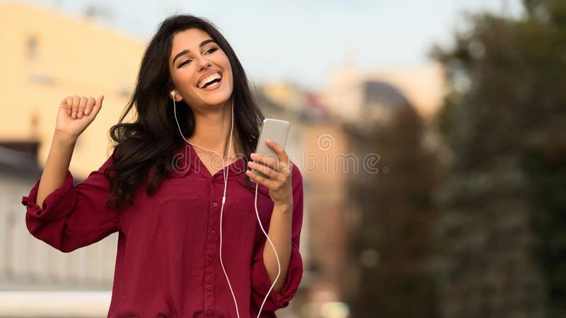 Happy girl dancing and listening music on the street stock images
