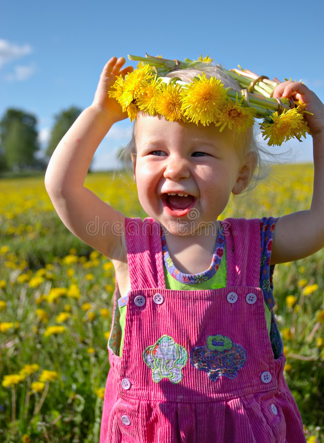 Happy girl with dandelion wreath royalty free stock photography