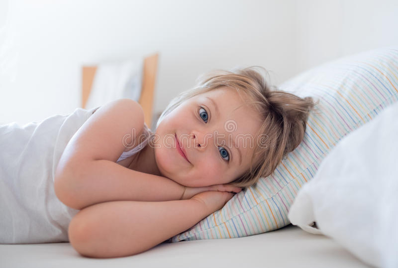 Happy girl daughter waking up smiling looking at camera on parent`s bed at morning. Happy relaxed family life with. Children at home. Bright sunny light royalty free stock photo