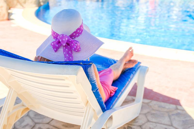 Happy girl on a deckchair by the pool by the sea royalty free stock photography