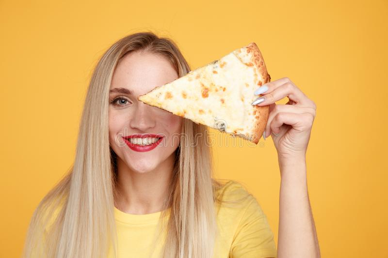 Happy girl with delicious cheese pizza isolated over the yellow background. stock photo