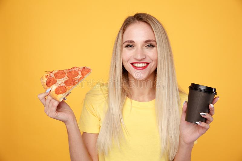 Happy girl with delicious pizza and a cup of coffee isolated over the yellow background. stock photography