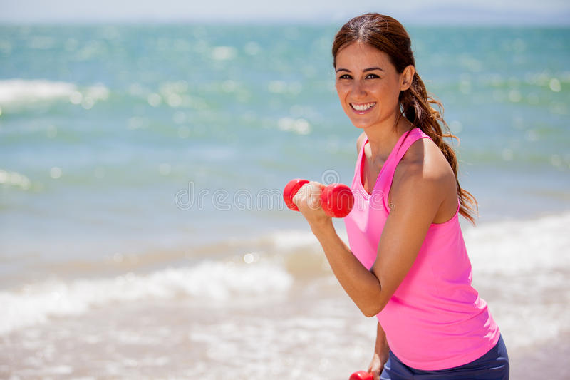 Happy girl doing some exercise. Cute young woman exercising and lifting some weight at the beach stock photos