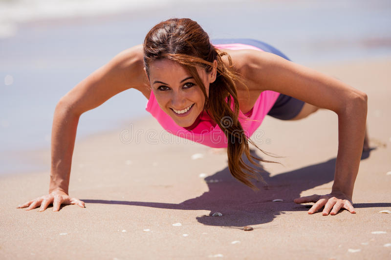 Happy girl doing some push-ups. Cute Latin woman exercising and doing some push-ups at the beach royalty free stock image