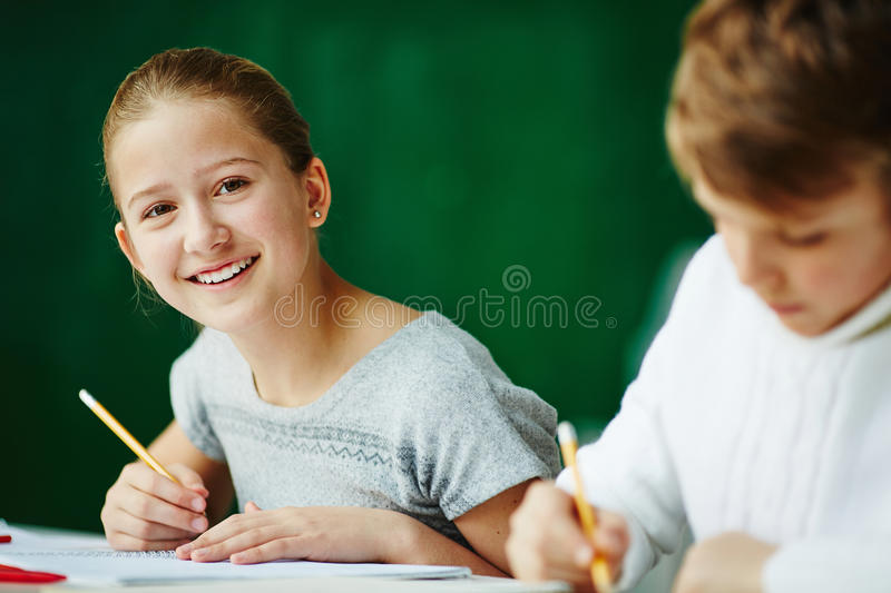 Happy girl drawing. Happy schoolgirl looking at camera while drawing with classmate near by stock photography